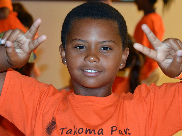 Youth camper displaying peace sign with both hands
