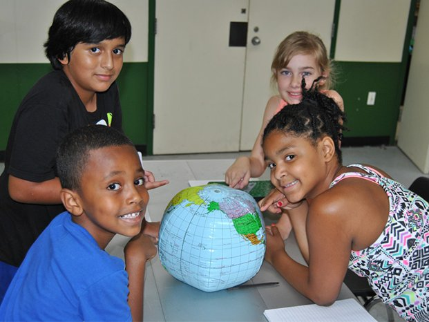Youth with globe at After the Bell program