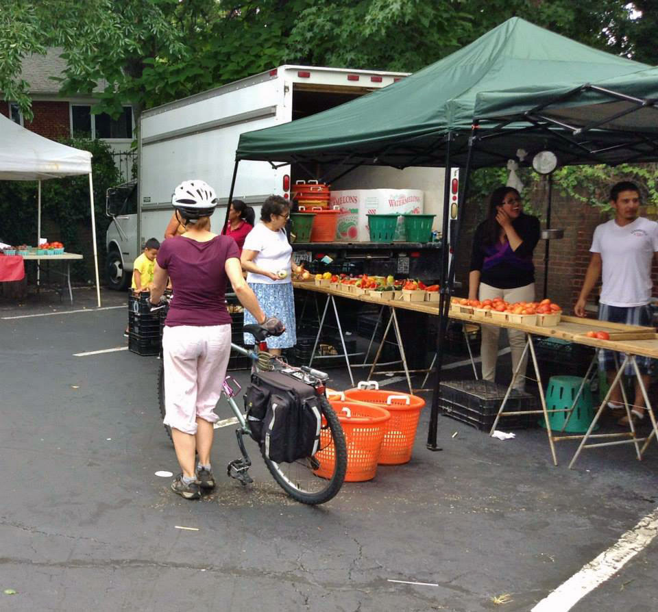 A shopper peruses the fruits and vegetables for sale at the Crossroads Farmers Market.